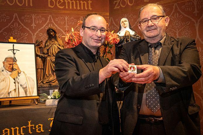 Prietser Wim Vangheluwe (links) en pastoor André Monstrey met het relikwie met haar van paus en heilige Johannes Paulus II. (in de achtergrond)