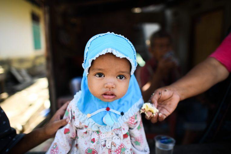 Een verdwaasd kind krijgt wat te eten in Wani. Beeld AFP