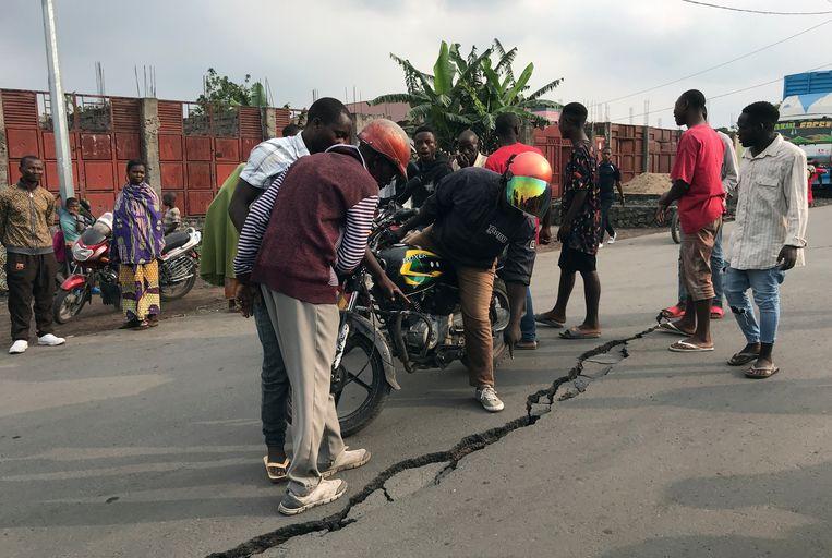 De lavastroom stopte aan de rand van hun stad, maar de inwoners van Goma in het oosten van Congo merken nog altijd dat de vulkaan Nyiragongo een uitbarsting achter de rug heeft. De naschokken zorgen voor scheuren in het wegdek in de straten van Goma.  Beeld REUTERS