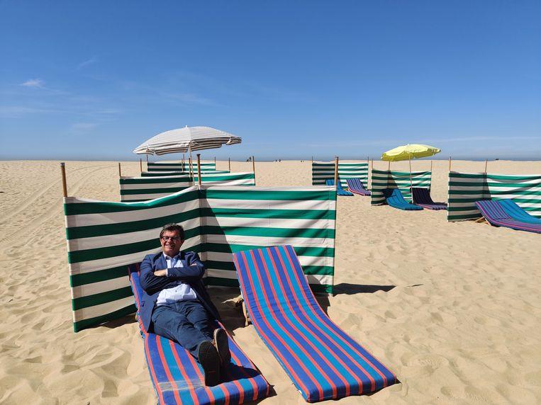 Burgemeester Bart Tommelein demonstreert de social-distancingmaatregelen op het strand van Oostende.  Beeld BELGA