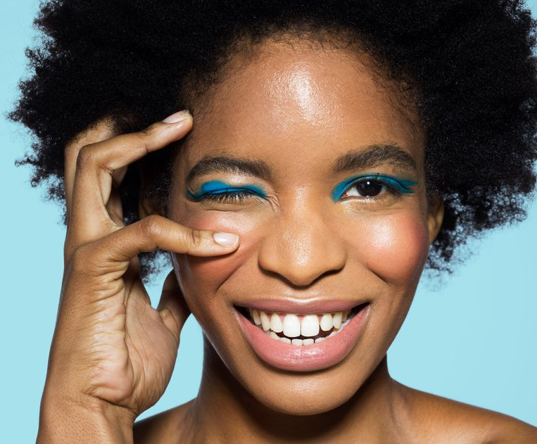 Close-up of young mixed-race woman looking to camera, smiling, wearing blue eye make-up, with hand near eye, with turquoise background Beeld Getty Images