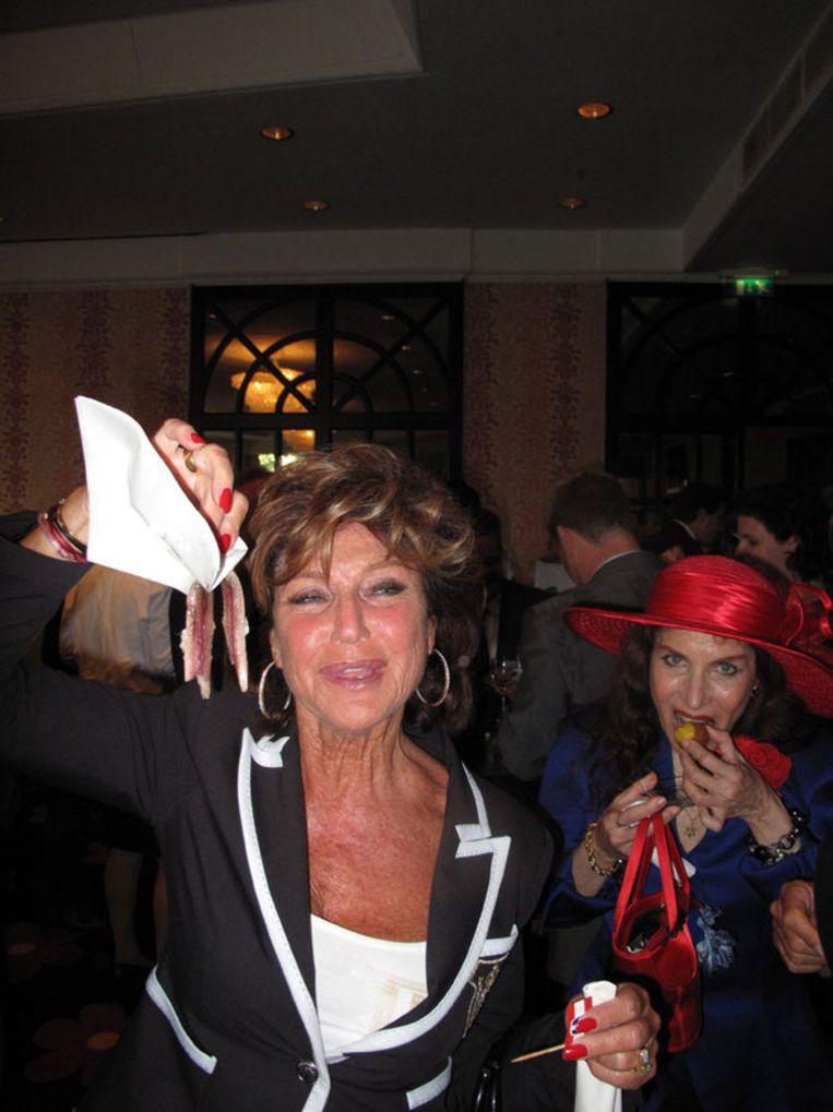 Societylady Netty van der Veer wil geen vieze vingers. Achter haar met  hoed: Yorina de buikdanseres. Beeld null