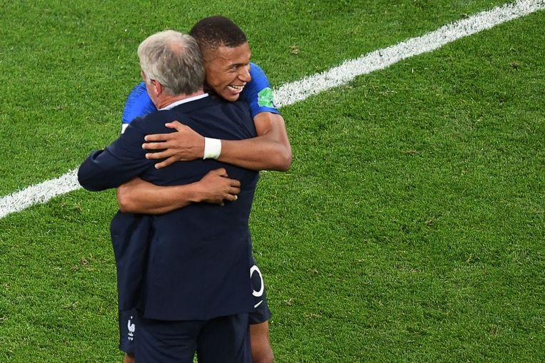 De Franse coach Didier Deschamps omhelst zijn sleutelspeler Kylian Mbappé na de zege tegen België in de halve finale. Beeld AFP
