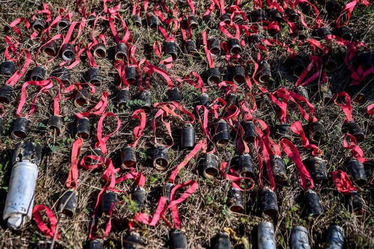 Tientallen niet-ontplofte clusterbommen uitgestald op een veld. Ze vormen een ritmisch uitgebalanceerd tableau des doods, met de vrolijk rode linten van hun parachutes als verbindend element. Beeld Aris Messinis/AFP