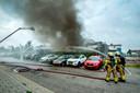 Brandweerlieden zijn druk bezig met het blussen van de brand van poelier Blom aan de Westervoortsedijk. Rechts op de foto de witte gevel van de islamitische slachterij New Atlas.