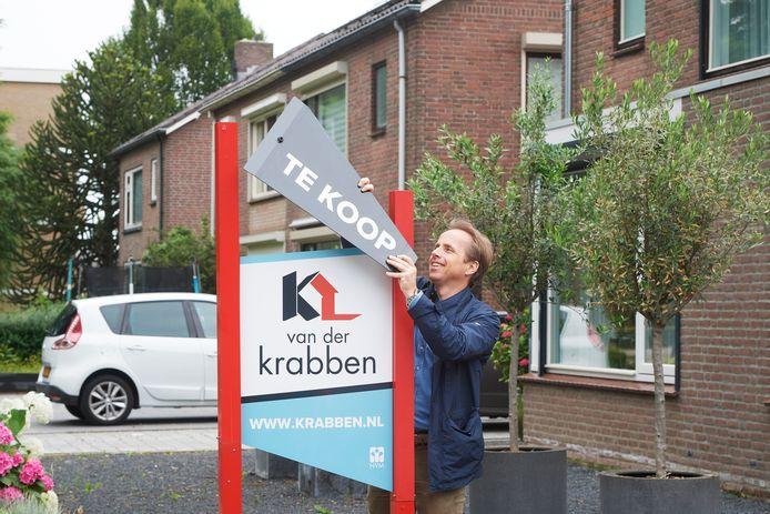 Makelaar Joris Welten van het Osse makelaarskantoor Van der Krabben plaatst een verkoopbord bij weer een huis dat te koop gezet is. Reële kans dat de vraagprijs overboden wordt.