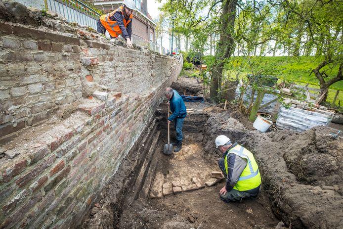 Archeoloog Maarten Wispelwey (met schop) legt de fundering van een historisch rondeel bloot bij de ingestorte stadsmuur van Elburg.
