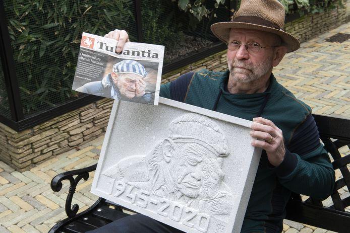 Kunstenaar Rinus Floors werd geraakt door een foto van een Auschwitz-gevangene, in Tubantia. Na een lange speurtocht kreeg hij officieel toestemming de foto te gebruiken. Hij maakte er een plaquette van.