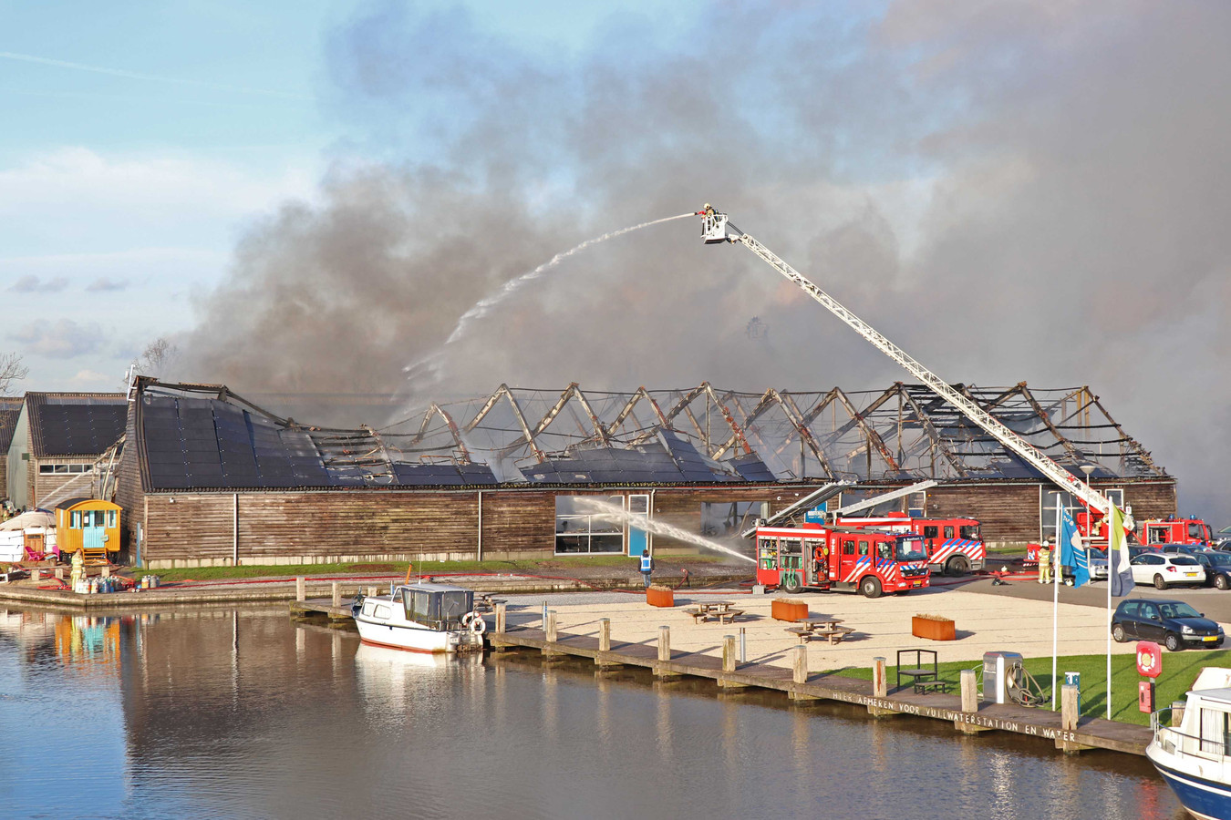 Brandweerlieden blussen de brand in de loodsen bij de IJsselsteinse jachthaven Marnemoende.