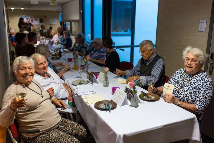 Bewoners Door, Wil en Ank (vlnr) hebben zojuist hun voorgerecht op en genieten van een wijntje tijdens het diner in de gang van Nieuwehagen.