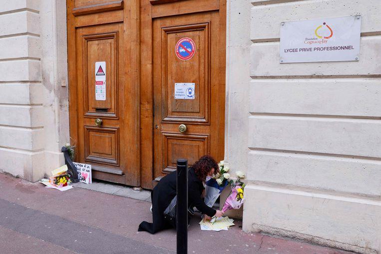 Een vrouw legt bloemen bij een school in Argenteuil, bij Parijs, nadat het lichaam van een 14-jarig meisje was gevonden in de Seine.   Beeld AFP