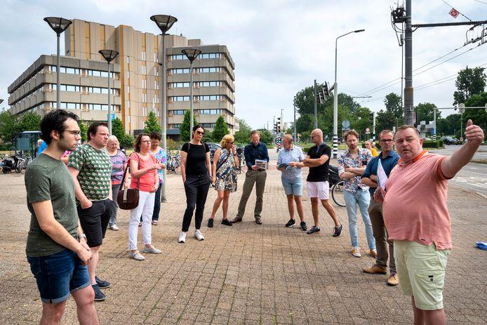 Leden van de Arnhemse gemeenteraad laten zich door Jeroen Reussing (r) bijpraten over toekomstige ontwikkelingen in de wijk Kronenburg, die niet allemaal in goede aarde vallen bij omwonenden.