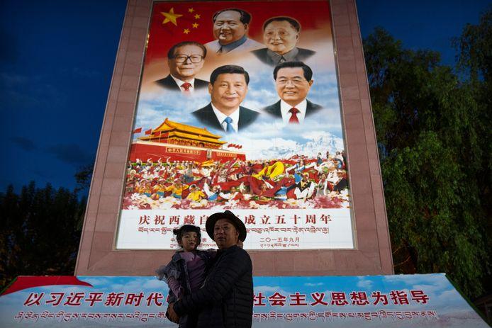 Un homme tient une fille dans ses bras alors qu'ils posent pour une photo devant une grande fresque représentant le président chinois Xi Jinping, en bas au centre, et d'autres dirigeants chinois sur une place publique au pied du palais du Potala à Lhassa, dans la région autonome du Tibet, dans l'ouest de la Chine. Le dirigeant chinois Xi Jinping a effectué une rare visite au Tibet alors que les autorités renforcent les contrôles sur la culture bouddhiste traditionnelle de la région himalayenne, accompagnés d'une accélération du développement économique et de la modernisation des infrastructures.