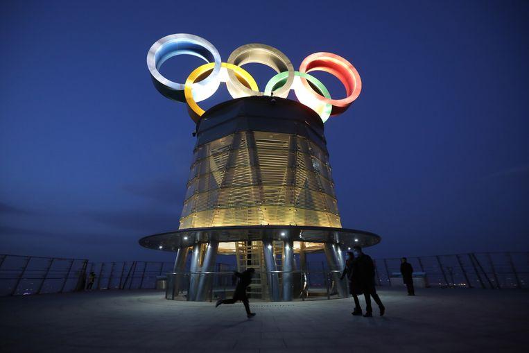 Mensen lopen langs  de Olympische toren in Beijing.  De Olympische Winterspelen vinden van 4 tot en met 20 februari 2022 in de Chinese hoofdstad plaats.  Beeld EPA