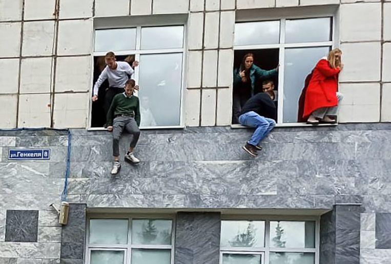 Studenten springen uit de ramen van de universiteit om aan de schutter te ontkomen. Beeld Hollandse Hoogte / Sputnik