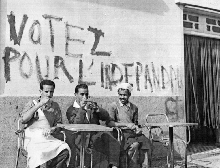 Algiers, 1962. Algerijnen drinken koffie voor een pro-onafhankelijkheidsleus. Beeld AFP
