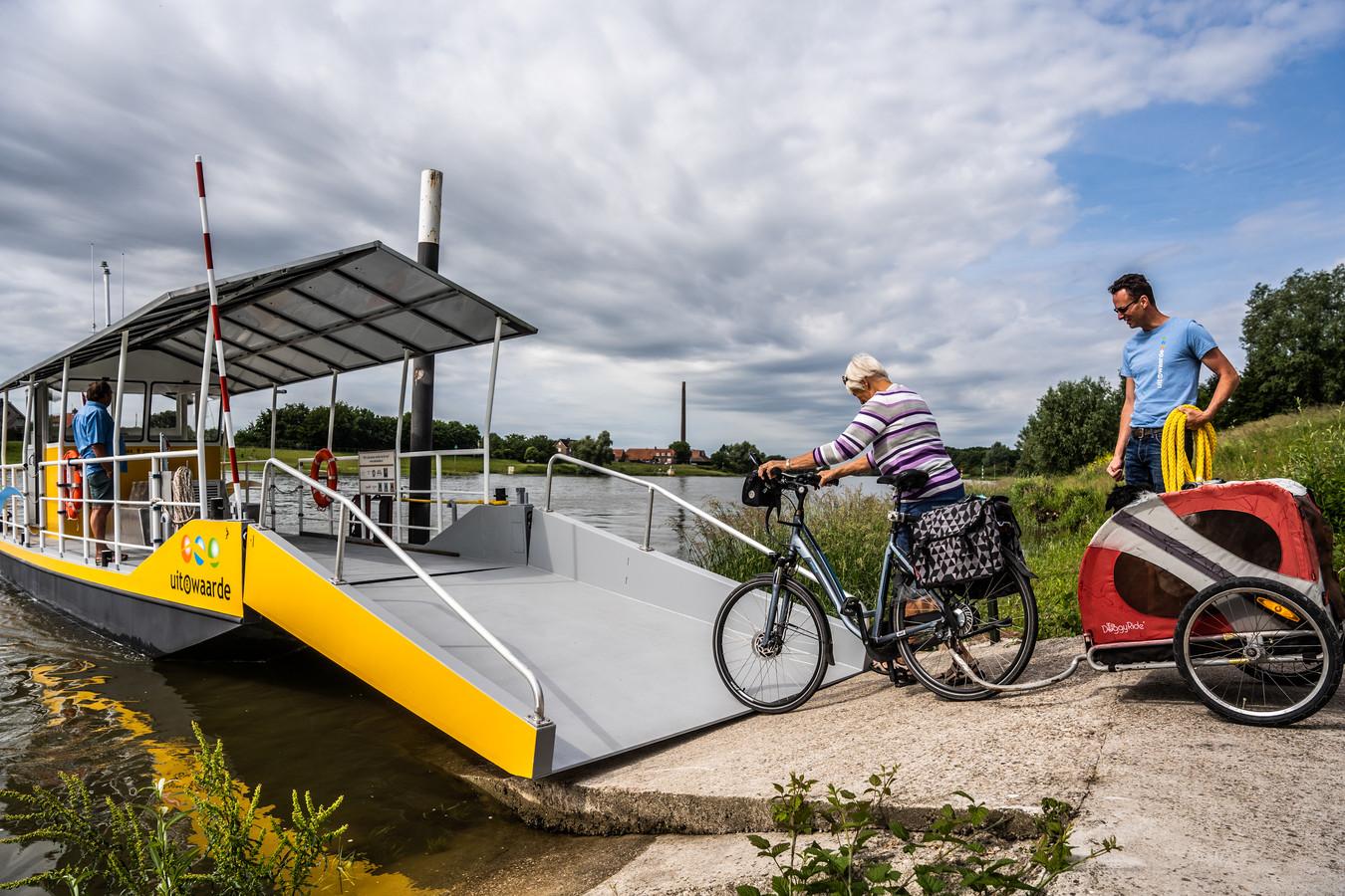 Henri Kooijmans helpt de eerste passagiers - dame en hond uit Den Helder - aan boord van de Henri-1, het nieuwe fiets- en voetveer tussen Renkum en Heteren.