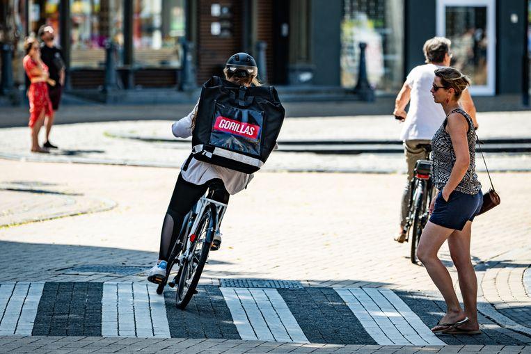 'De bezorgers in deze branche hebben vaak maar 5 tot 8 minuten de tijd om de bestelling op locatie te brengen, dus er rust een enorme druk op hen om snoeihard door de stad te crossen op hun elektrische fietsen.' Beeld Hollandse Hoogte/Novum RegioFoto