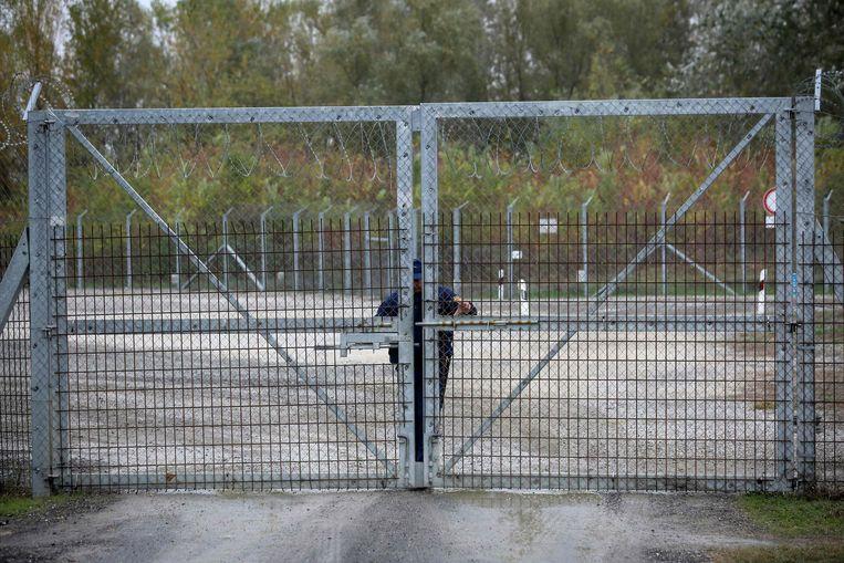 Een Hongaarse politieman sluit een hek bij een transitzone aan de grens met Servië. Beeld AFP
