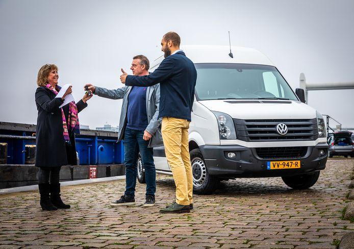 Suzan de Groot (links) ontvangt namens Koos Bakker (midden) en Jeroen Markusse (rechts) de sleutels van hun nieuwe busje.