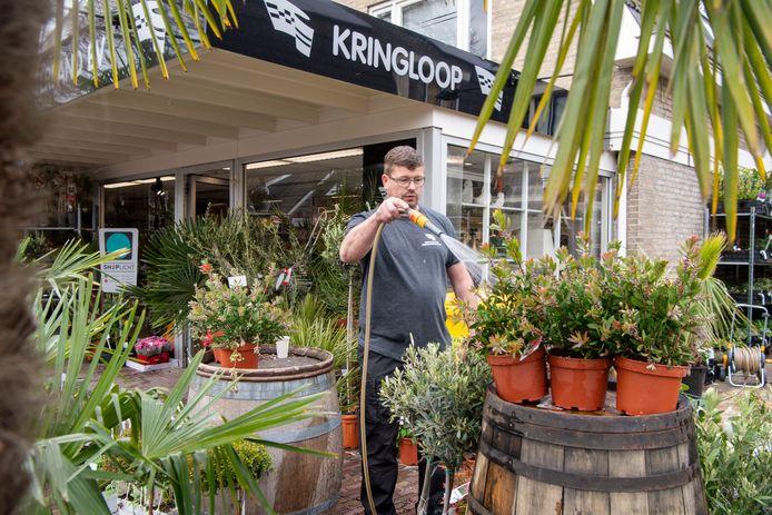 Jeroen van Hasselt geeft de planten bij de nieuwe winkel in Nieuwleusen water.