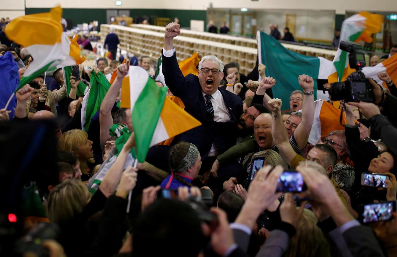 Sinn Féin-aanhangers nemen een kandidaat op de schouders in een stembureau in Cork.  Beeld Reuters