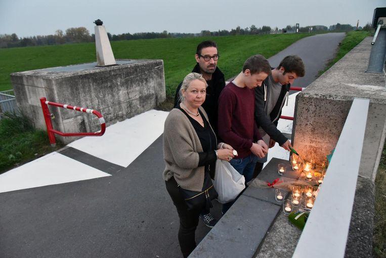 Schoondochter Angelique, zoon Danny en kleinzonen Branko en Yanosh branden kaarsen op de plaats waar Raymond Goossens verongelukte aan de fietssluis in Schellebelle.