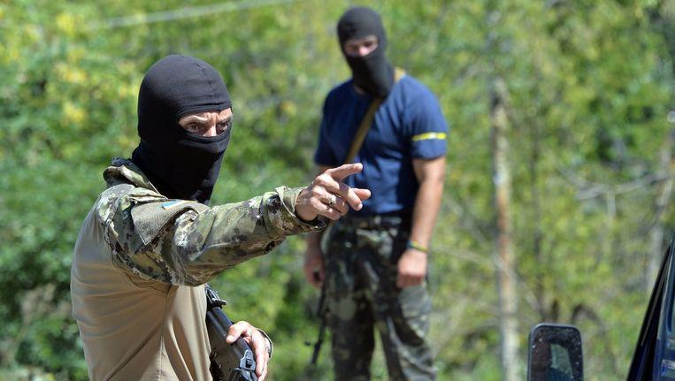 Separatisten controleren auto's bij een checkpoint voor de stad Lisichansk, in het oosten van Oekraïne. Beeld AFP