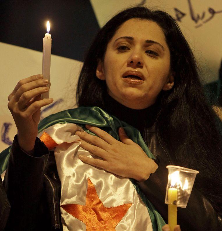 Een Syrische vrouw houdt een kaarsje omhoog en een Syrische revolutievlag vast, in Beirut, Libanon. Beeld ap