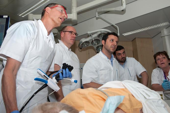 De MDL-artsen Robert Laheij (l.) en Robbert Eichhorn volgen via een beeldscherm de ingreep. Ze werken daarbij onder supervisie van de ervaren dr. Luca Cirillo (midden).