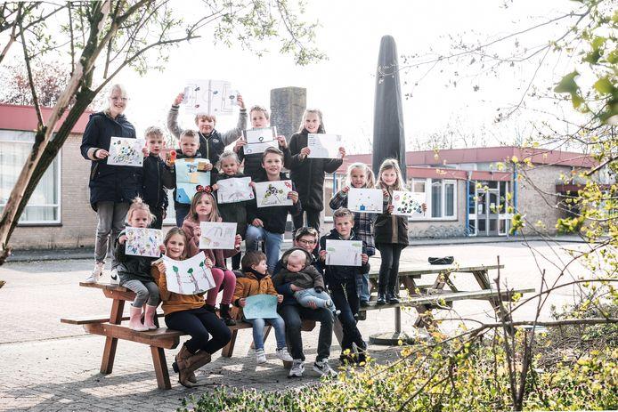 Kinderen met hun protest-tekeningen op hun schoolplein in Zevenaar.