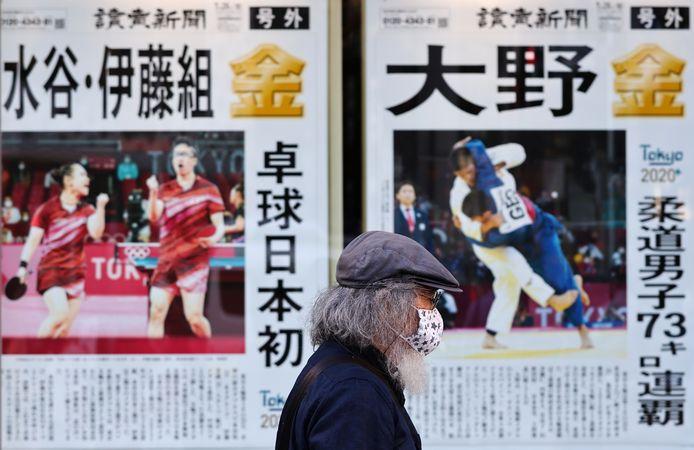 Een man met een mondmasker op loopt voorbije een display van een krant die over de Spelen bericht in Tokio. Daar geldt de noodtoestand wegens de pandemie.