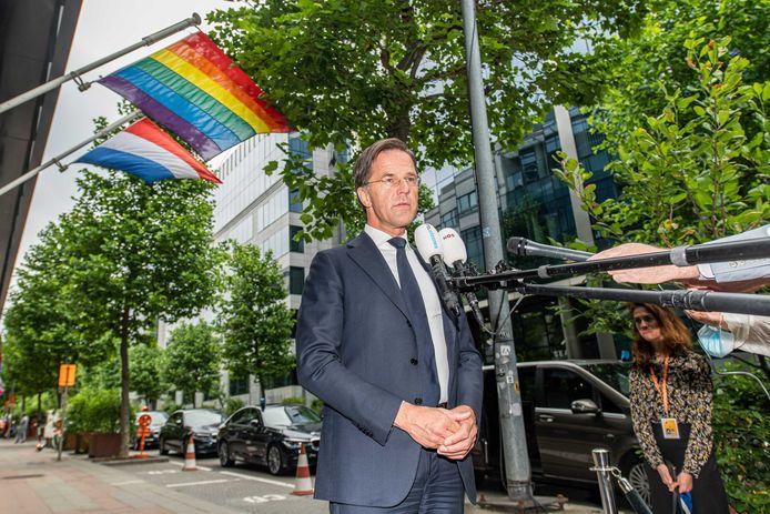 De Nederlandse premier Mark Rutte staat de pers te woord bij het gebouw van de Nederlandse vertegenwoordiging in de EU voor de eerste dag van de Europese top. Achter hem heel bewust een wapperende regenbloogvlag.