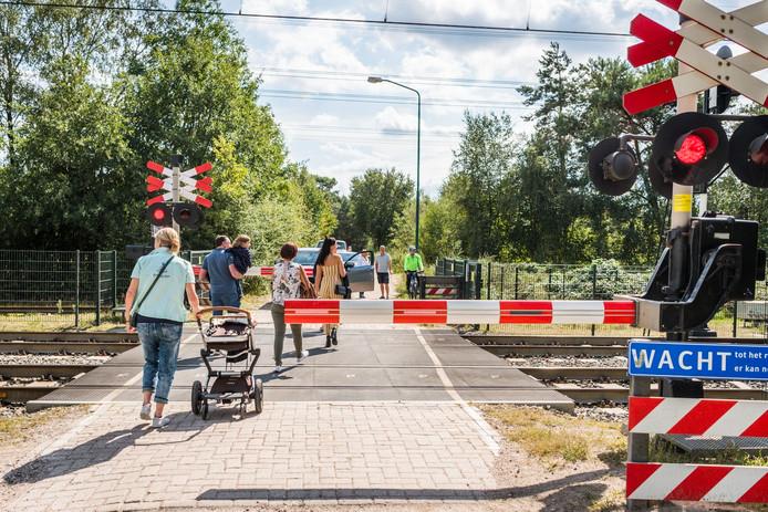 Al de hele dag steken mensen over bij de gesloten spoorwegovergang. Vijf uur lang is er een storing in Nuenen.