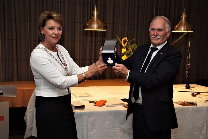 Voorzitter Jan Martens van Sociëteit Gezelligheid krijgt de Koninklijke Erepenning uit handen van burgemeester Elly Blanksma.