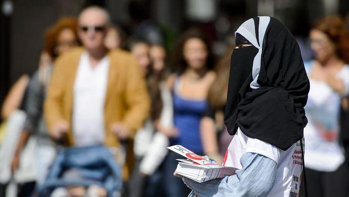 Nora Illi, lid van het Islam Centrum in Zwitserland, deelt folders uit over het referendum tegen het dragen van sluiers.