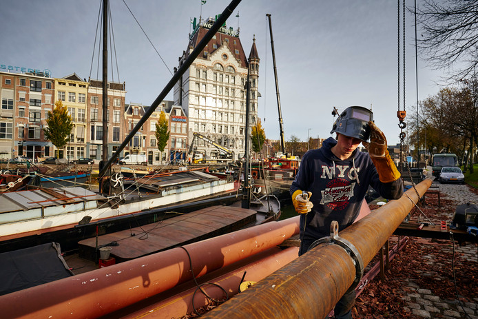 Een lasser werkt aan de giek van een historisch schip aan de Oude Haven.
