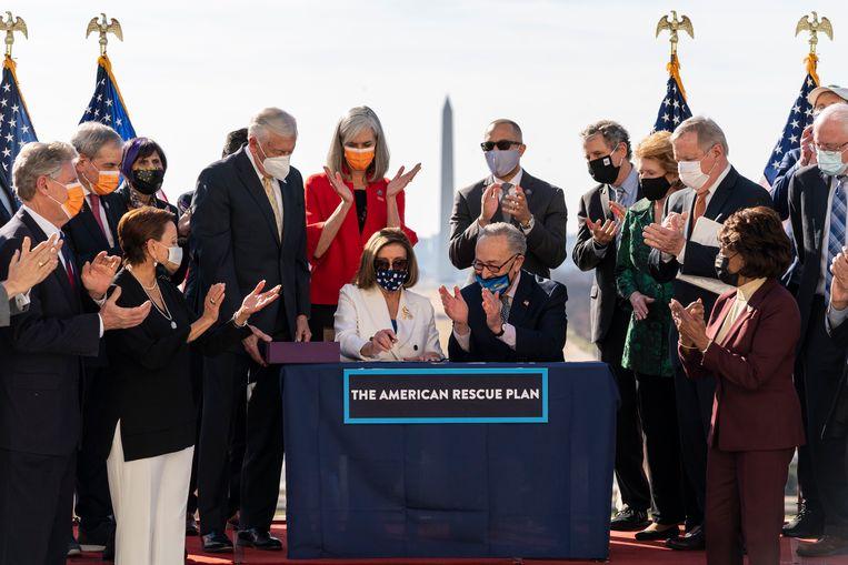 Applaus na het tekenen van de wet door Nancy Pelosi (Huis van Afgevaardigden) en Chuck Schumer (Senaat).  Beeld AP