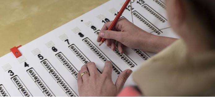 Mensen met een visuele beperking kunnen stemmen met een speciale mal en 'soundbox'.