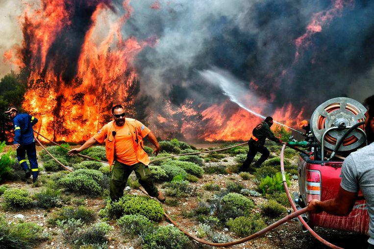 Brandweerlieden en vrijwilligers proberen het vuur te bestrijden in de buurt van Kineta, bij Athene. Beeld AFP