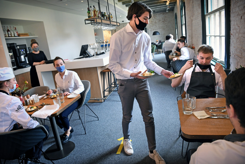 Leerlingen van de koksopleiding De Rooi Pannen in Breda aan het werk in de keuken van het onderwijshotel. Omdat er geen gasten in het hotel zijn vanwege de coronacrisis, eten de leerlingen zelf hun gerechten op.  Beeld Marcel van den Bergh / de Volkskrant
