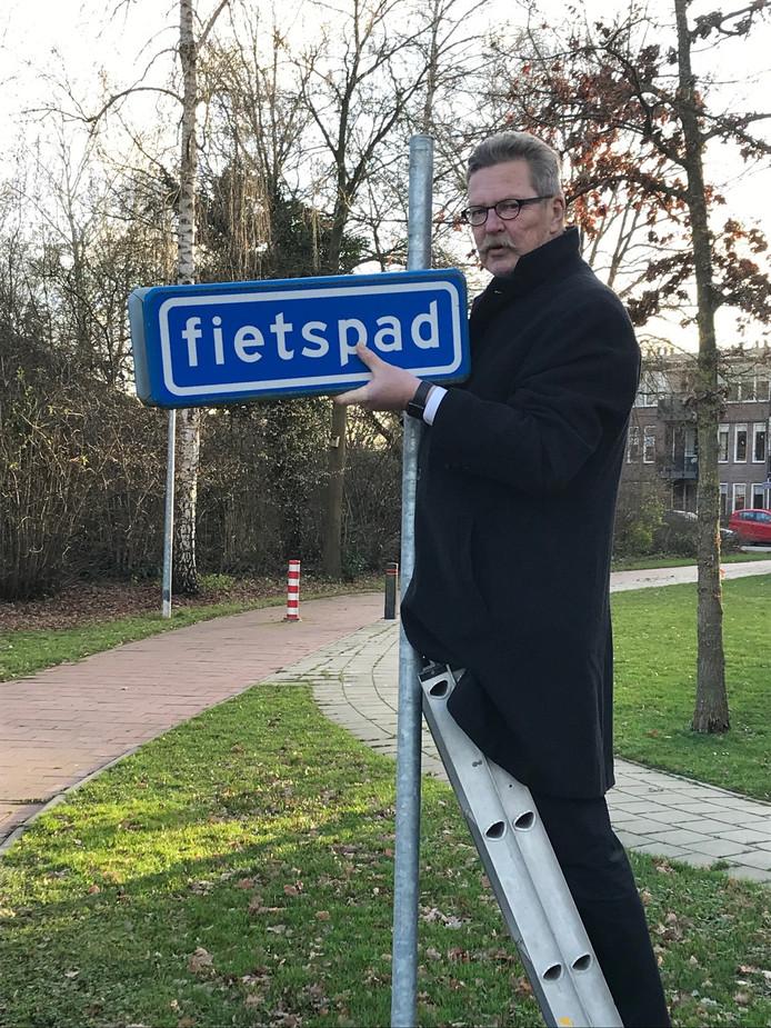 Verkeerswethouder Hans van der Sleen 'ontmantelt' een overbodig verkeersbord.