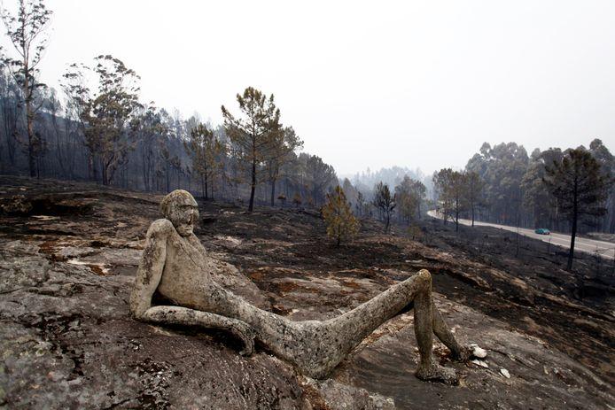 Een sculptuur is zwartgeblakerd door de natuurbrand in Spanje.