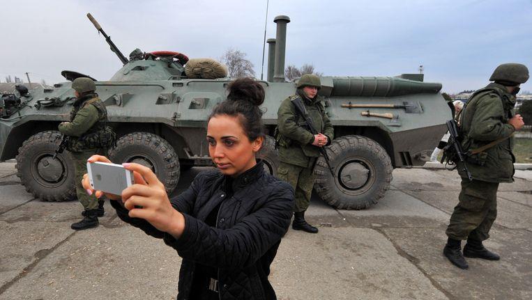 Een vrouw neemt een selfie in de door Russen bezette havenplaats Feodosiya op de Krim. Beeld AFP