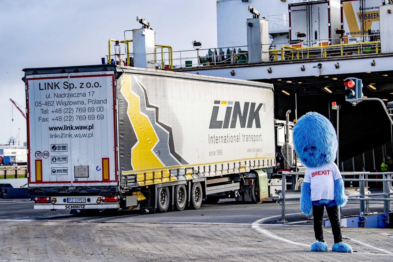 Het 'brexitbeest', een mascotte van de Get Ready For Brexit campagne, deelt flyers uit aan vrachtwagenchauffeurs in de haven van Rotterdam. Beeld ANP