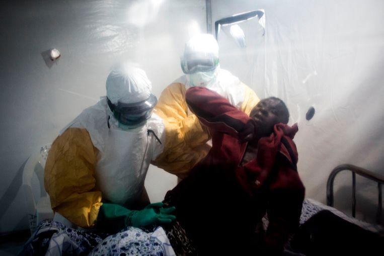 Twee medici behandelen een ebola-patiënt. Beeld AFP
