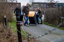 De bewoners sjouwen hun containers van hun woning naar de Bandijk.