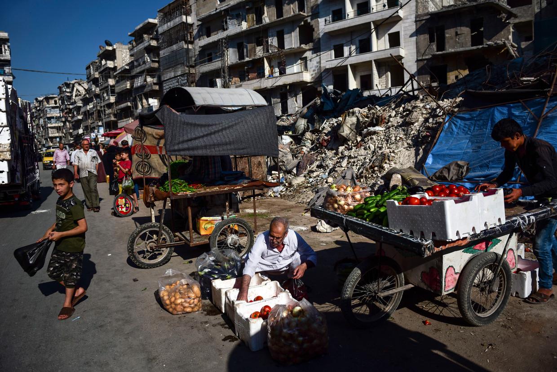In Oost-Aleppo brengen Syriërs groenten en fruit aan de man.De stad moet nog grotendeels heropgebouwd worden. Beeld NYT MERIDITH KOHUT