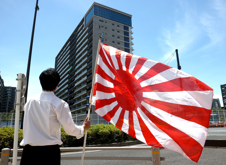 Een Japanner draagt de vlag met de rijzende zon. Die wordt in delen van Azië geassocieerd met oorlogsagressie. Beeld EPA