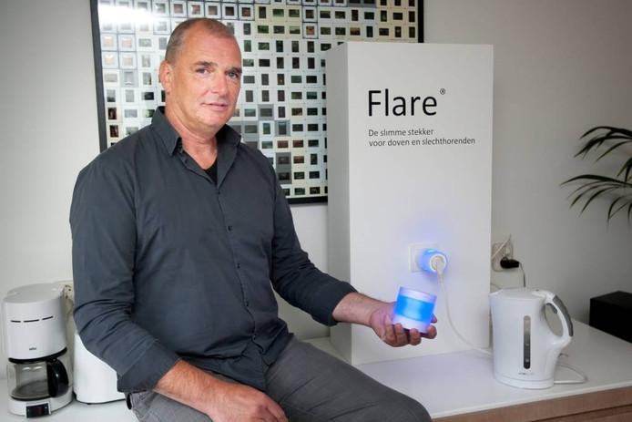 Ontwerper Edwin de Kuiper met zijn stekker en verklikker. De kleur blauw geeft aan dat het apparaat uit staat.